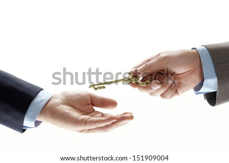 businessman hand holding a key and handing it over to another man. Hands and key on white background.  - stock photo