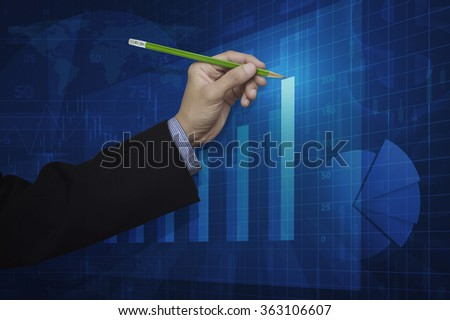 Businessman hand holding a pencil pointing at growth graph, Success business concept, Elements of this image furnished by NASA