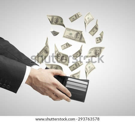 businessman hand holding a purse from which emerge dollars