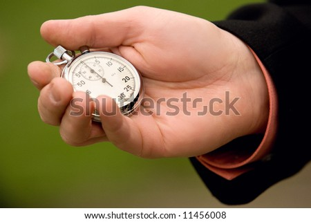 Businessman hand holding a stopwatch over green