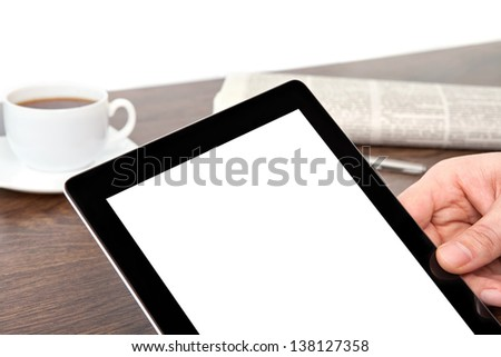 businessman hand holding a tablet with isolated screen against the background of the table in the office - stock photo