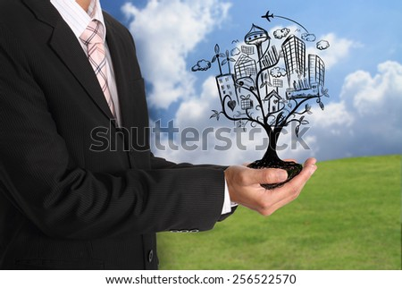 Businessman hand holding abstract tree illustration with city lifestyle concept - stock photo