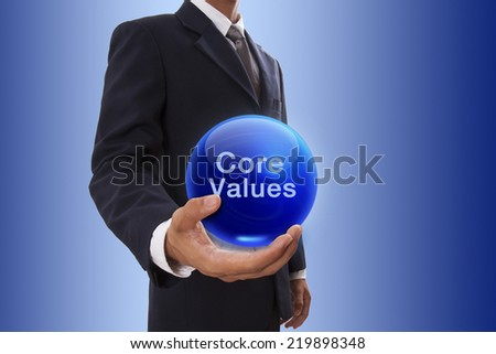 Businessman hand holding blue crystal ball with core values word. - stock photo