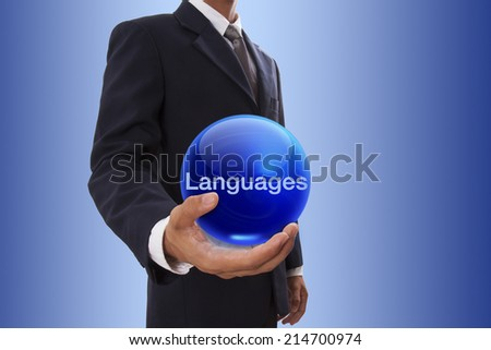 Businessman hand holding blue crystal ball with languages word. - stock photo