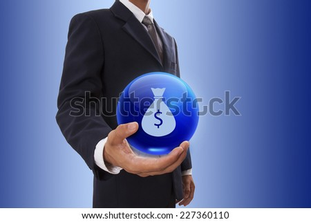 Businessman hand holding blue crystal ball with money bag with US dollar sign. - stock photo
