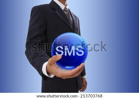 Businessman hand holding blue crystal ball with SMS word.  - stock photo