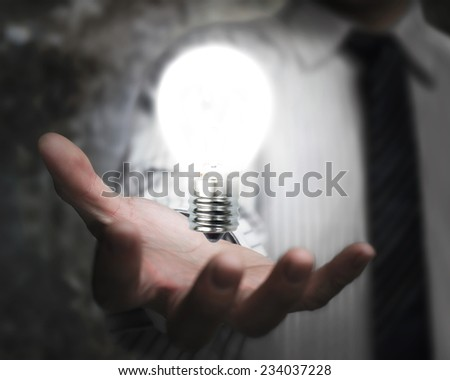 businessman hand holding brightly light bulb illuminated dark background - stock photo