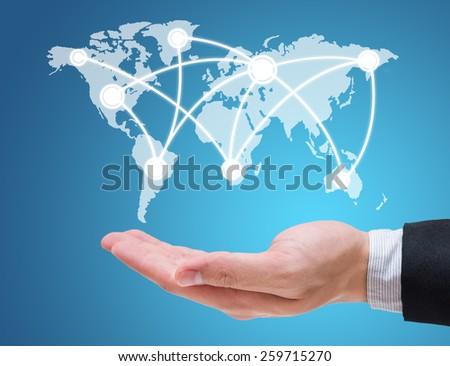 Businessman hand holding globe map isolated on blue background - stock photo
