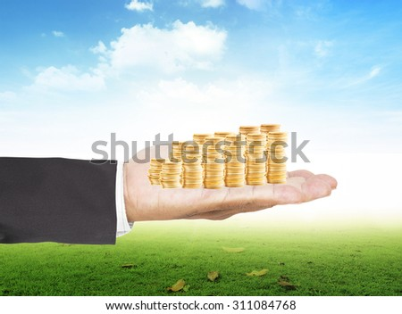 Businessman hand holding golden coins over beautiful nature background. Money coin concept. - stock photo