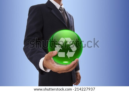 Businessman hand holding green crystal ball with recycle logo.