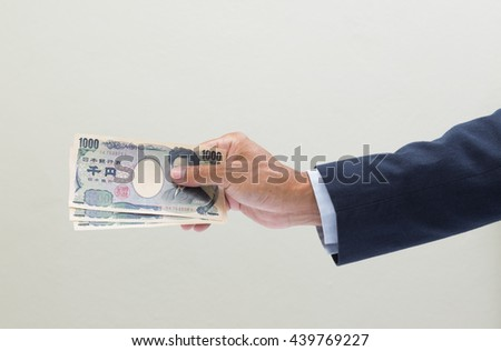 Businessman hand holding Japanese YEN banknote