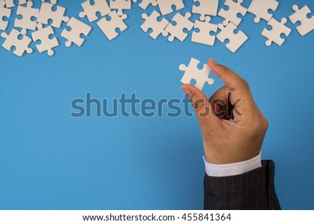 businessman hand holding jigsaw puzzle, blue background