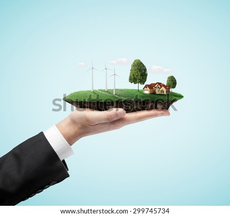 businessman hand holding landscape with eco wind turbine - stock photo