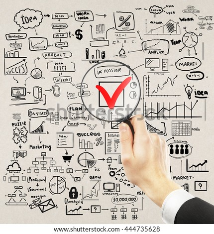 Businessman hand holding magnifier over red checkmark with business drawings around on concrete background. Nothing is impossible concept