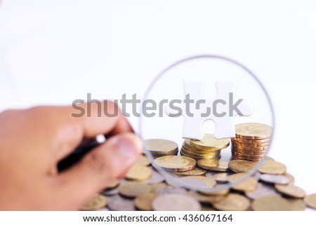 Businessman hand holding magnifying glass, white puzzle and gold coins with copyspace area - stock photo