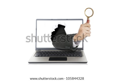 Businessman hand holding magnifying out from laptop computer - stock photo
