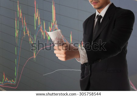 Businessman hand holding money and stock market graph and bar chart price display,Businessman failure in stock market - stock photo