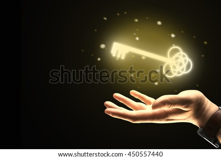 Businessman hand holding ornate golden key on dark background. Success concept