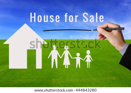 Businessman hand holding pen and message House for Sale with model of house and family on green grass field and blue sky background. Business concept in selling, building or purchase house property.  - stock photo