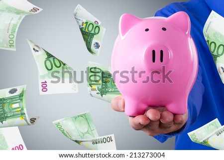 Businessman hand holding pink piggy bank and one hundred euro banknotes flying on dark background. - stock photo