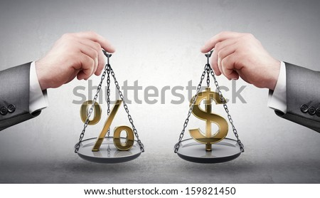 businessman hand holding Scale with procent symbols and symbols of currencies US dollar  - stock photo