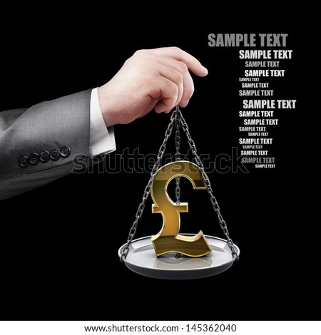 businessman hand holding Scale with symbols of currencies pound isolated on black background  - stock photo