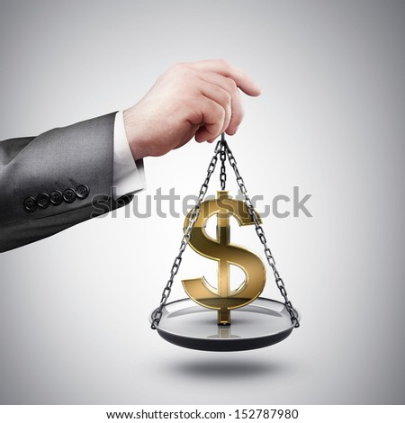 businessman hand holding Scale with symbols of currencies US dollar  - stock photo