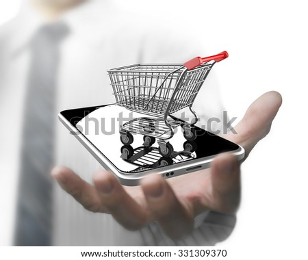 Businessman hand holding shopping cart with smart phone, on line shopping concept. - stock photo