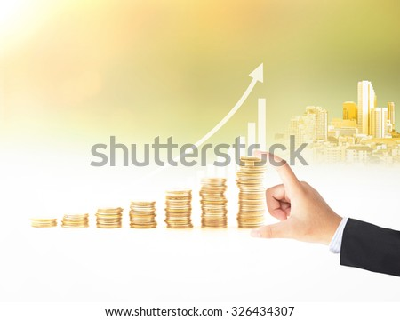 Businessman hand holding stacks of coins over graph finance and the city over blurred sunset background. Growth concept. Investment concept.