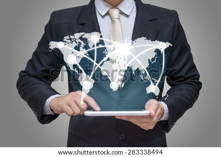 Businessman hand holding tablet global marketing on gray background - stock photo