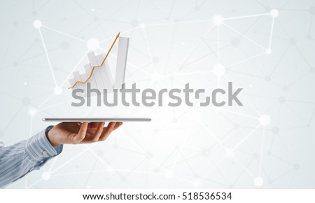 Businessman hand holding tablet with finance graph on screen
