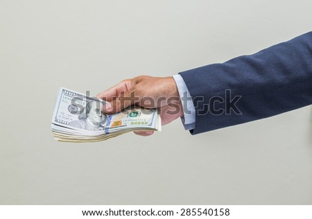 Businessman hand holding us dollar banknote
