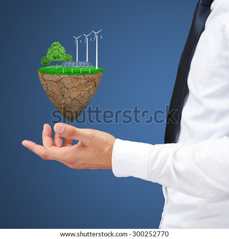 Businessman hand holding wind power station mills and trees on the lawn. Natural concept. - stock photo