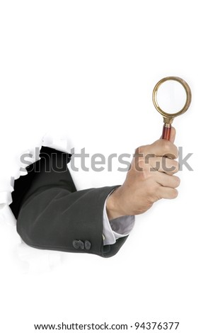 Businessman hand investigate breaking through a paper wall holding  a magnifying glass - stock photo