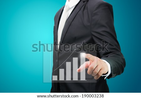 Businessman hand point financial symbols growth on blue background - stock photo
