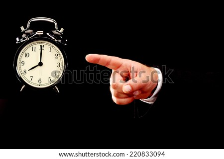 Businessman hand pointing alarm clock. Time for work concept - stock photo