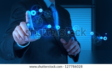 businessman hand pointing to the  gear to success as concept - stock photo