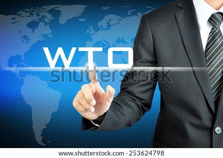 Businessman hand pointing to WTO (or World Trade Organization) sign on virtual screen