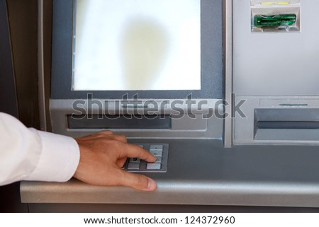 Businessman hand pressing a key in the keypad of a cash machine, outdoors. - stock photo