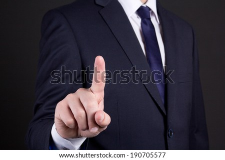 businessman hand pressing an imaginary button on over dark background