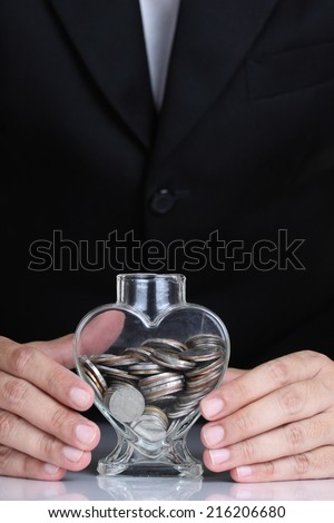 Businessman hand protect money for safe investment in the future. - stock photo