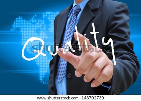 businessman hand pushing quality button on a touch screen interface  - stock photo