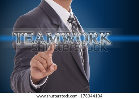 Businessman hand pushing teamwork button on virtual screens   - stock photo