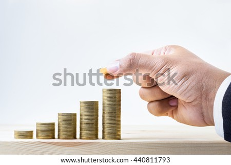 Businessman hand putting gold coin to stack growing on wood.For business growth and financial concept