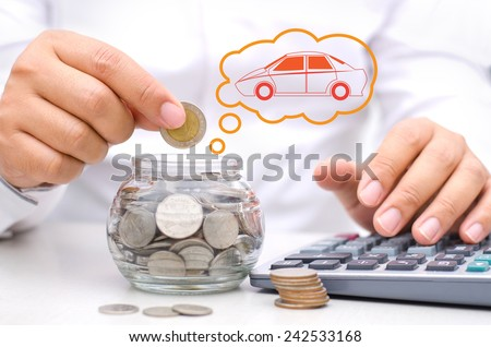 businessman hand putting money coins into glass piggy bank for buy car - stock photo