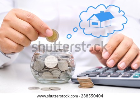 businessman hand putting money coins into glass piggy bank for buy home  - stock photo