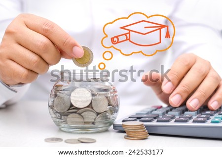 businessman hand putting money coins into glass piggy bank for Education