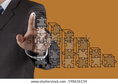 businessman hand puzzle charts with new modern computer and business strategy as concept  - stock photo