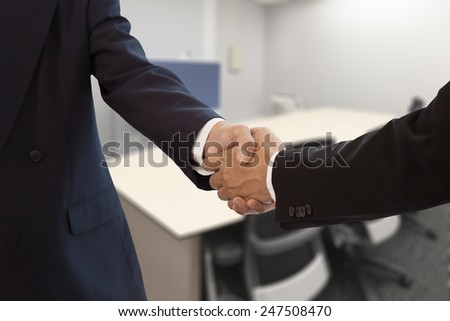 Businessman hand shake in a meeting room - stock photo