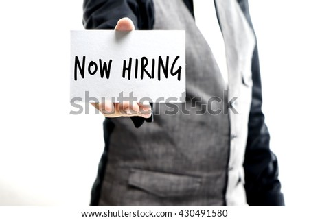 "Businessman hand showing card with ""Now Hiring"" message - stock photo"